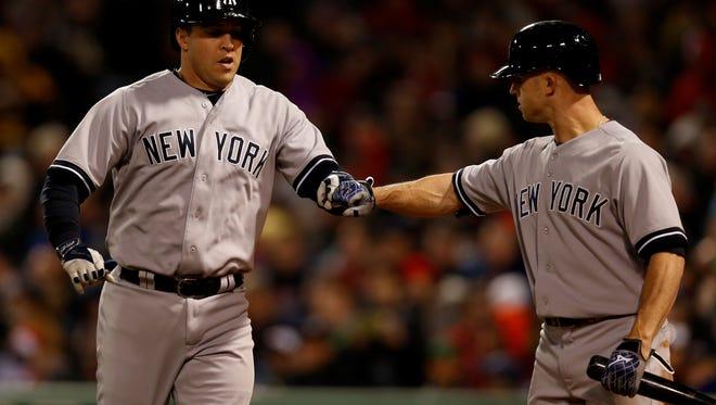 Yankees first baseman Mark Teixeira, left, is congratulated by left fielder Brett Gardner  after hitting a home run off Boston Red Sox pitcher Felix Doubront  during the third inning at Fenway Park Thursday night.