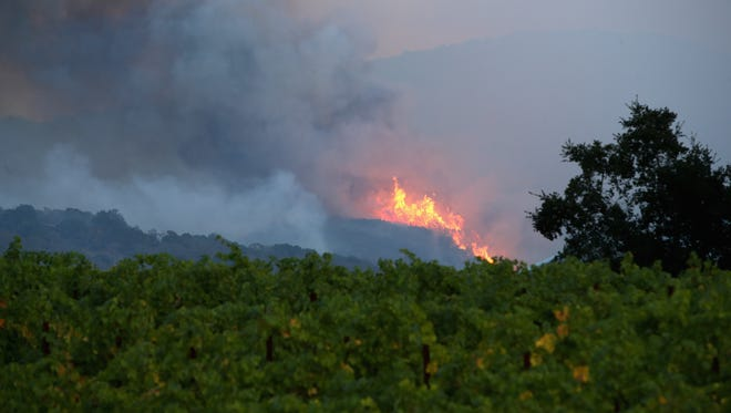 A fire breaks out in the hills above a vineyard at the Atlas Fire on Oct. 10, 2017 in Napa, Calif.