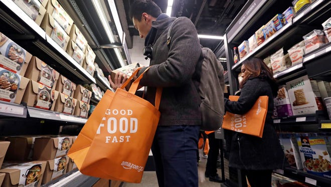 Customer Paul Fan shops at an Amazon Go store on Jan. 22, 2018, in Seattle. The store on the bottom floor of the company's Seattle headquarters allows shoppers to scan their smartphone with the Amazon Go app at a turnstile, pick out the items they want and leave. The online retail giant can tell what people have purchased and automatically charges their Amazon account.
