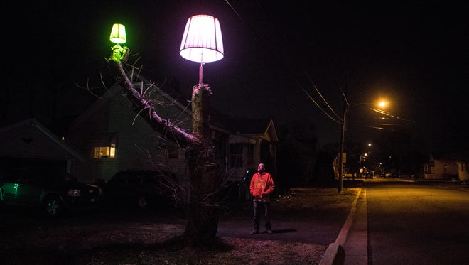 Bob Colegrove stands next to the giant lampshade he built onto a dead tree in his front yard on Baltimore Avenue in Wilmington. Colegrove changes the colors of the bulbs to match various seasons and holidays throughout the year.