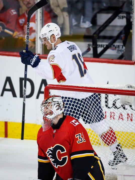 Florida Panthers' Aleksander Barkov, top, of Finland, celebrates a Panthers goal as he skates behind Calgary Flames goalie Jon Gillies during the third period of an NHL hockey game Saturday, Feb. 17, 2018, in Calgary, Alberta. (Jeff McIntosh/The Canadian Press via AP)
