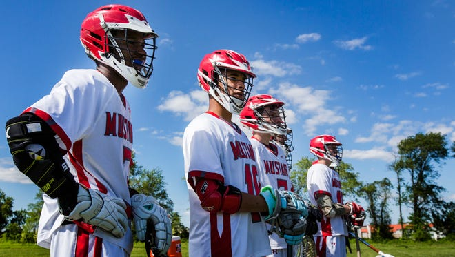 MOT's Tre Tillman (second from left) stands at his team's bench with teammates in the first half of MOT Charter School's 17-3 win over First State Military Academy at MOT Charter School in Middletown on Wednesday afternoon.