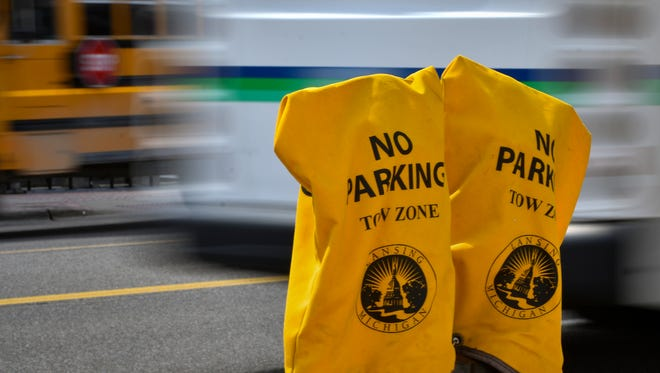 About 10 parking spaces in front of The Lansing Center are flagged as no parking zones Tuesday, April 10, 2018.