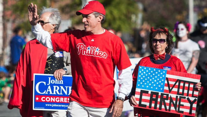 U.S. Representative John Carney waves to the crowd as he walks in the Newark Halloween Parade on Sunday afternoon, October 26, 2014.