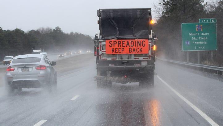 A state DOT truck spreads salt along Interstate 195