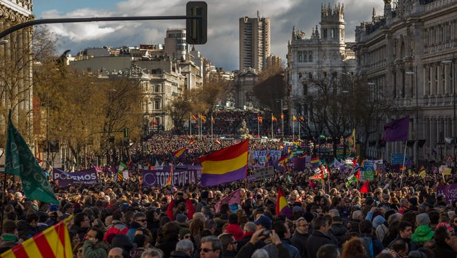 People wave Republican and Podemos party flags during a Podemos (We Can) party march in Madrid, Spain, Saturday, Jan. 31, 2015.
