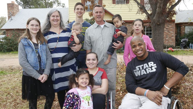 The Rybergs gather with eight of their 13 children outside their home in Queen Creek on Jan. 7, 2017: (clockwise from left)  Grace, 13; mother Lori, holding Obie. 2; Jeremiah, 18; father Nate, holding Gabe; Hope, 16; John, 33; Faith, 19; and Mercy, 3.