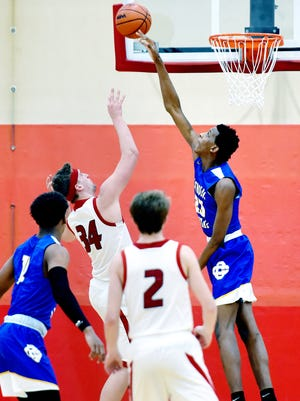 Catholic Central High School senior forward and Michigan State University commit Marcus Bingham Jr., right, blocks a shot by Allendale's Mason Vredeveld during the second half of Central's game against Allendale on Tuesday, Jan. 16, 2018, at Allendale High School.