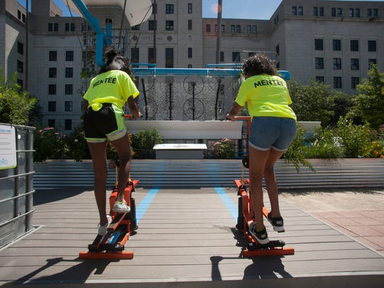 Brianna Pearson, right,  and Asia Young, both 12, use peddle pumps to activate water jets and turn the fountain wheels at Roosevelt Plaza Park. In keeping with the environmentally-friendly spirit of the park, the fountain wheels are made up of recycled bicycle wheels and the pop-up is surrounded by an edible garden, thereby encouraging visitors to incorporate sustainable practices and healthy choices into their lives.