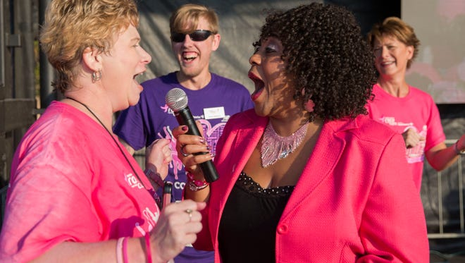 Sheila Seiler, the executive director of the local Komen for the Cure sings 'We are Family' with Gina Moore as they get the crowd ready to start the 5k during the Susan G. Komen Race for the Cure on Sunday morning.