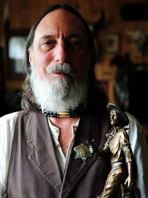 PaleWolf Brunelle, known by most as Tom Rickman, is seen with the trophy that he received for being inducted into the Cowboy Action Shooters Hall of Fame for almost a quarter-century of service to the Single Action Shooting Society.