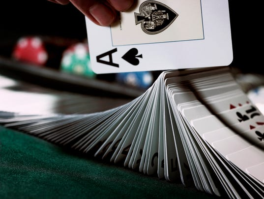 Croupier turning pack of cards on gaming table with ace, close-up