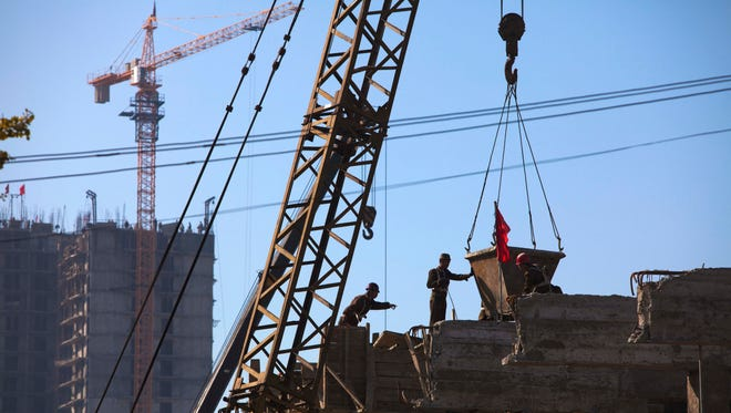 In this Tuesday Oct. 11, 2011 photo, North Korean construction workers guide in a large bucket of cement to the roof of a building in the Mansudae area of Pyongyang, North Korea.