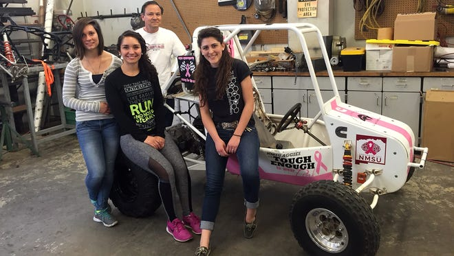 Members of New Mexico State University's Pink Baja team, (front row from left) Lindsay Martinez, Jaymie Velasquez and Caitlynn Roy and adviser Ken Rubble are shown with the car they are preparing to race in a SAE Mini Baja competition in late April in Tennessee.