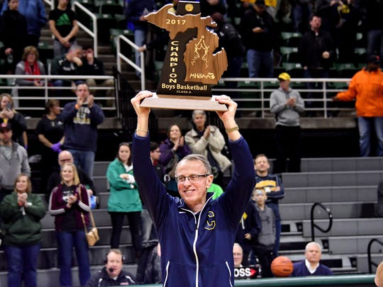 Dan Fife raises his first state championship trophy as coach at Clarkston.