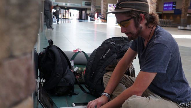 Ethan Lindhout of Fort Collins, Colo., sits inside the Reno-Tahoe International Airport while working on his laptop. Lindhout, a videographer, will be documenting work on a Burning Man art installation.
