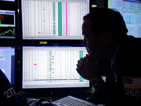A specialist is silhouetted with screens at his post on the floor of the New York Stock Exchange.