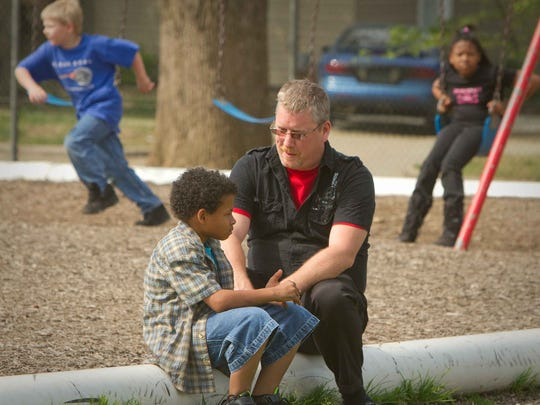 Robberson Elementary School Principal Kevin Huffman interacts with students while supervising the playground after lunch.