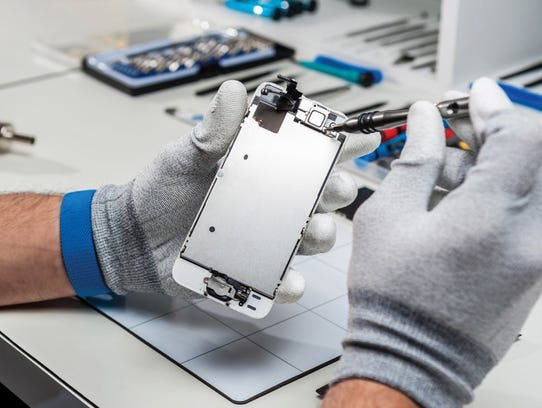 Technician replacing the screen of a used smartphone.