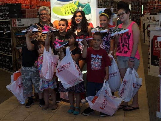 """Miss Cumberland County Olivia Cruz is joined by children who were able to pick out a pair of sneakers funded through her """"Love through Laces"""" project."""