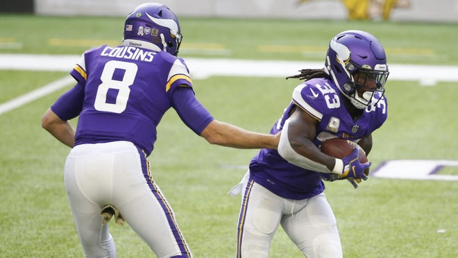 Minnesota Vikings quarterback Kirk Cousins (8) hands the ball off to running back Dalvin Cook (33) during the first half of an NFL football game, Sunday, Nov. 8, 2020, in Minneapolis.