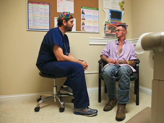 Dr. Will Cooke has been the lone doctor in Austin who has been treating those with HIV and AIDS.Dr. Will Cooke talks with HIV patient Jonathan Clark during a visit to the clinic.