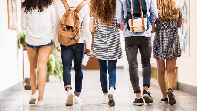 Teenage students in high school hall.