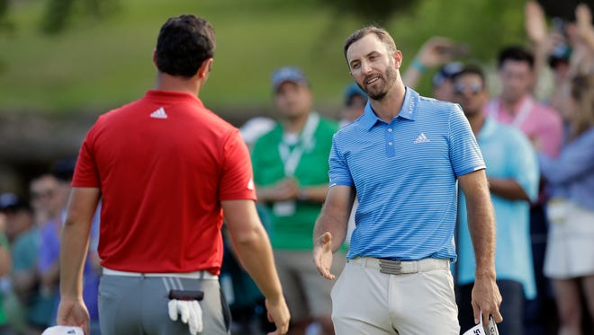 Dustin Johnson, right, reaches out to Jon Rahm, left, of Spain, after Johnson's win in the final pairing of the Dell Technologies Match Play golf tournament at Austin County Club, Sunday, March 26, 2017, in Austin, Texas.