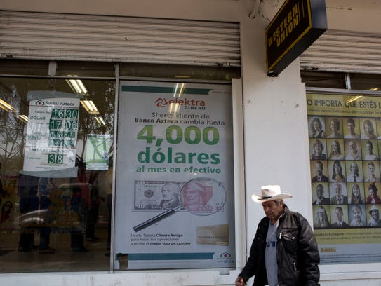 A man walks past signs advertising money transfer services