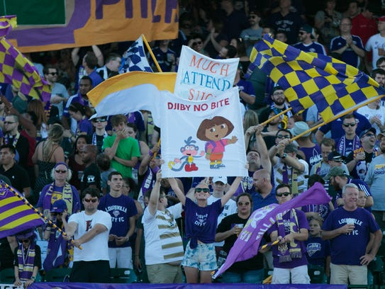 Louisville City FC fans hold up signs in reference