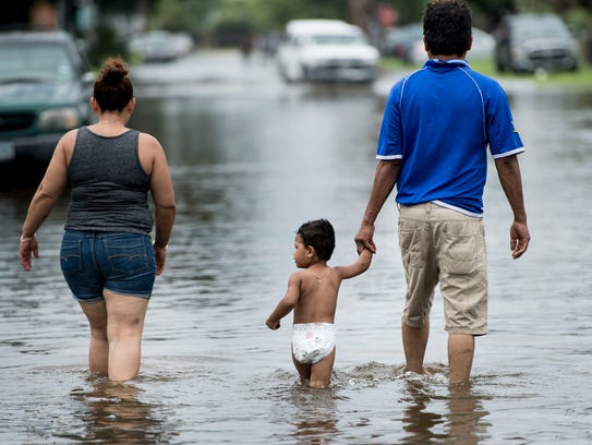 People walk through flooded streets as the effects