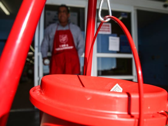 Money sticks out of the kettle Wednesday as Michael Sanchez rings his bell for the Salvation Army's Red Kettle Campaign outside a San Angelo Walmart.