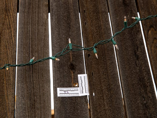 An evidence marker outlines a bullet hole in a fence Thursday at a home on Riverstone Road in Farmington.