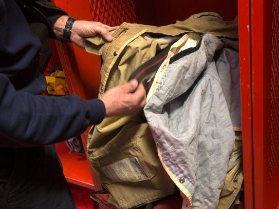 Ben Thorsheim, Farmington Fire Department engineer and personal protective equipment ccvoordinator, points about some of the features in firefighting coats on Thursda at Farmington Fire Department Station One in Farmington.