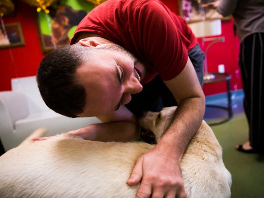 Daniel Campbell bends over to pet his new dog, Nyla,