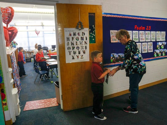 At left, Second grade teacher Dorothy Reese prepares for her class on Friday at Sacred Heart Catholic School in Farmington.
