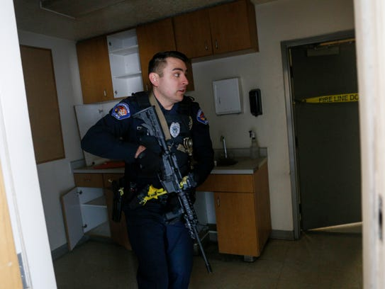 Farmington police Officer James Prince clears a room during an active-shooter exercise on Wednesday at a hangar at the Four Corners Regional Airport in Farmington.