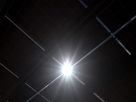 The sun shines between solar panels on Monday, March