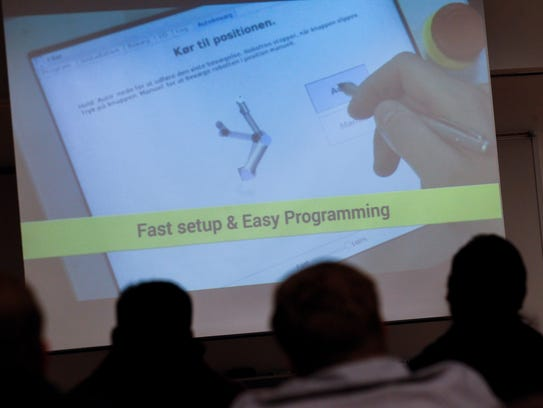 Audience members watch a video on robotics Tuesday at the San Juan College Quality Center for Business in Farmington.
