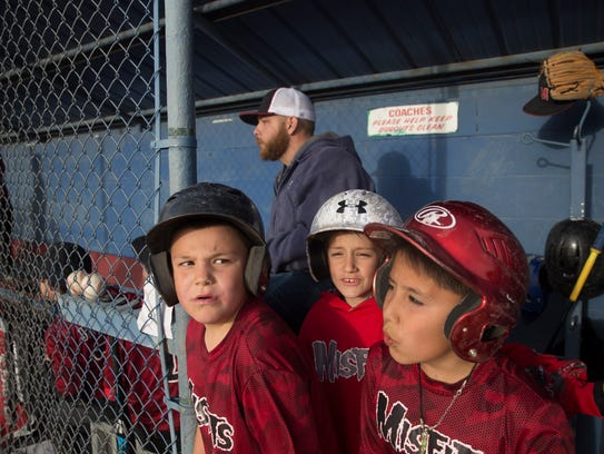 Bloomfield Youth Baseball players Joseph Olsen, left, Dax Heckman and Ben Lewis cheer on their team the Misfits during a game on Thursday at the city fields on South 1st Street in Bloomfield.