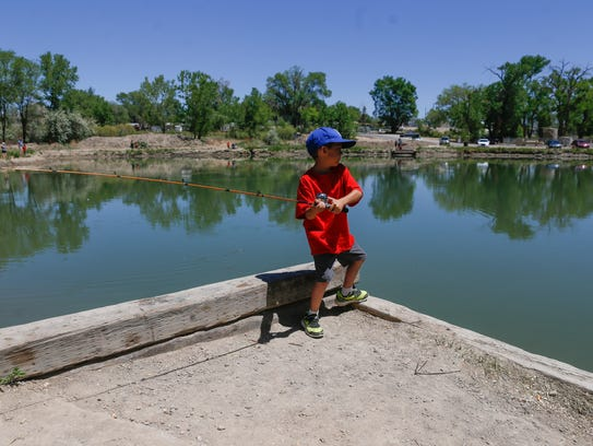 Student Anthony Red casts his line Friday at Riverside Pond in Aztec.
