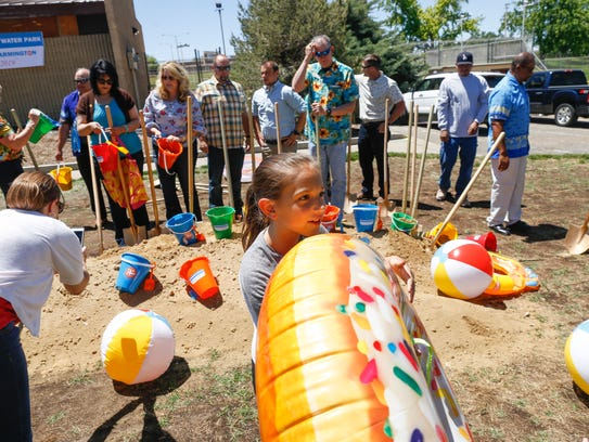 Madyson West, center, picks an inflatable doughnut float to take home Thursday after a groundbreaking ceremony for the Brookside Bay Water Park in Farmington.