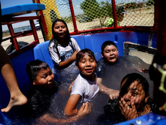 Valarie Castillo, top, Makah Russell, middle left, Gaberiel Russell, Devan Lizer and Christian Yazzie cool off in the dunk tank Monday during a summer kick off event, Summer Celebration, hosted by the Shiprock Office of Diné Youth.