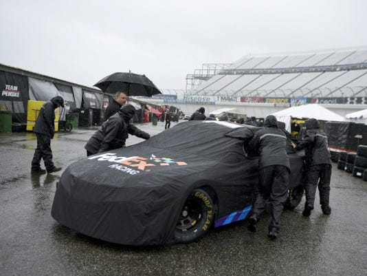Crew members push the race car of Denny Hamlin in the garage area for the NASCAR Sprint Cup series race Friday at Dover International Speedway in Dover, Del.