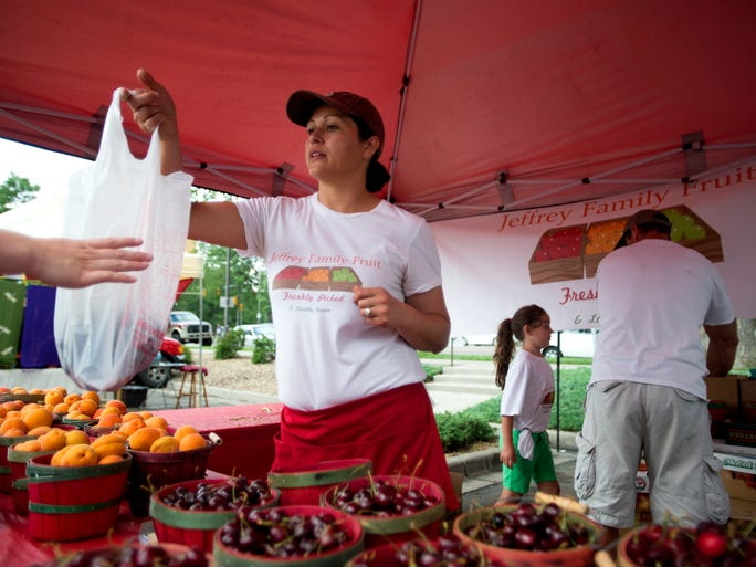Amparo Jeffrey sells cherries at the Larimer County Farmers' Market Saturday, July 12, 2014. The market is held every Saturday in the Larimer County Courthouse parking lot on the corner of Oak and Mason Streets from 8 a.m. to noon.