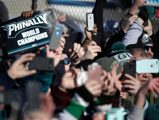 Philadelphia Eagles fan hold up smartphones as the team's airplane arrives at Philadelphia International Airport a day after defeating the New England Patriots in Super Bowl 52 in Minneapolis, Monday, Feb. 5, 2018. (AP Photo/Julio Cortez)