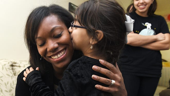 United Methodist Communications staff member Royya James, left, gets a thank-you kiss from Syrian refugee Ghadeer Nakshou, 5, after the girl received Christmas presents at her family's home in Nashville on Thursday, Dec. 17, 2015.