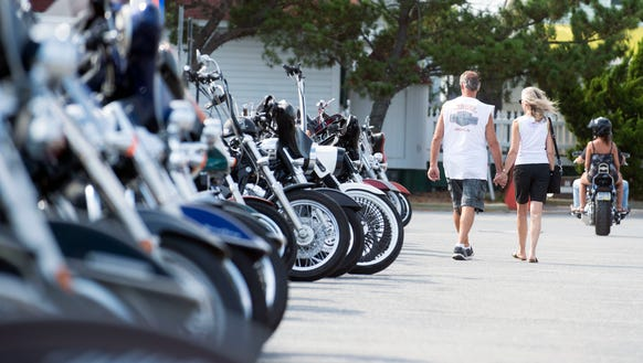 Visitors walk through rows of motorcycles parked in