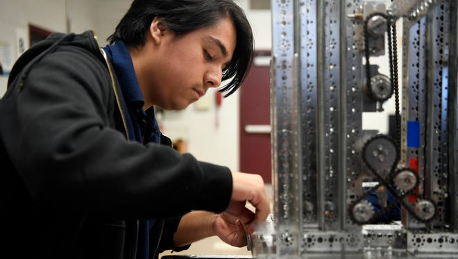 Jeferson Mendoza, a senior at the STEM School in John F. Kennedy High School, works on a robot in the robotics lab.