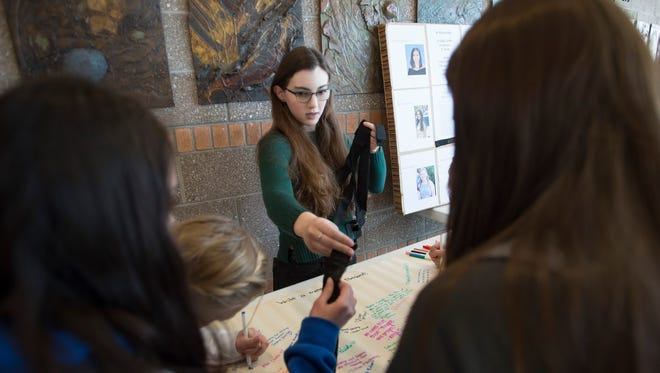 """Nina Shelanski hands out arm bands showing """"#MeNext?"""" during lunch at Poudre High School on Wednesday, February 21, 2018. T"""